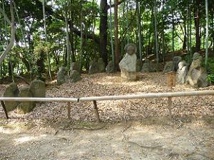 十八羅漢と書かれた石仏群。中央の石仏を囲むように小さな石仏が座っている。